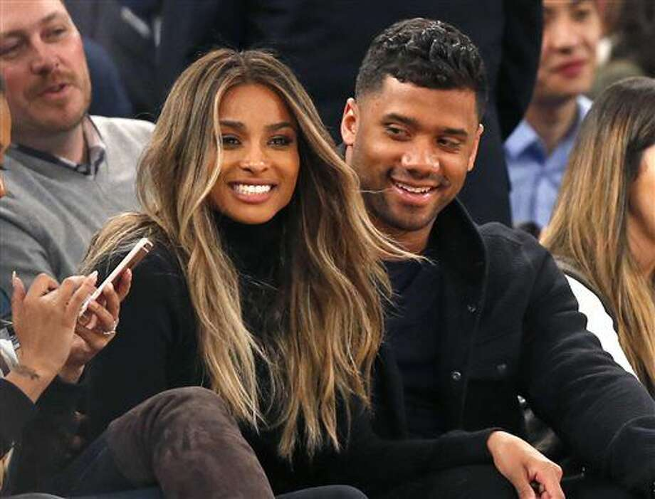 FILE - In this Feb. 9, 2016 file photo, singer Ciara, second from left, and Seattle Seahawks quarterback Russell Wilson sit courtside while attending an NBA basketball game between the New York Knicks and the Washington Wizards in New York. The couple were married Wednesday, July 6, 2016, at Peckforton Castle in Cheshire, England. (AP Photo/Kathy Willens, File) Photo: Kathy Willens