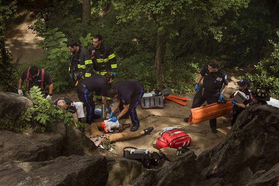 A man, center bottom, bleeds from his injured leg as he gets helped from paramedics, firemen, and police in Central Park in New York, Sunday, July 3, 2016. Police and emergency responders took the man on a stretcher from New York's Central Park after people near the area reported hearing some kind of explosion. Fire officials say it happened shortly before 11 a.m., inside the park at 68th Street and Fifth Avenue. Authorities say the man suffered serious injuries and was taken to the hospital. (AP Photo/Andres Kudacki) Photo: Andres Kudacki