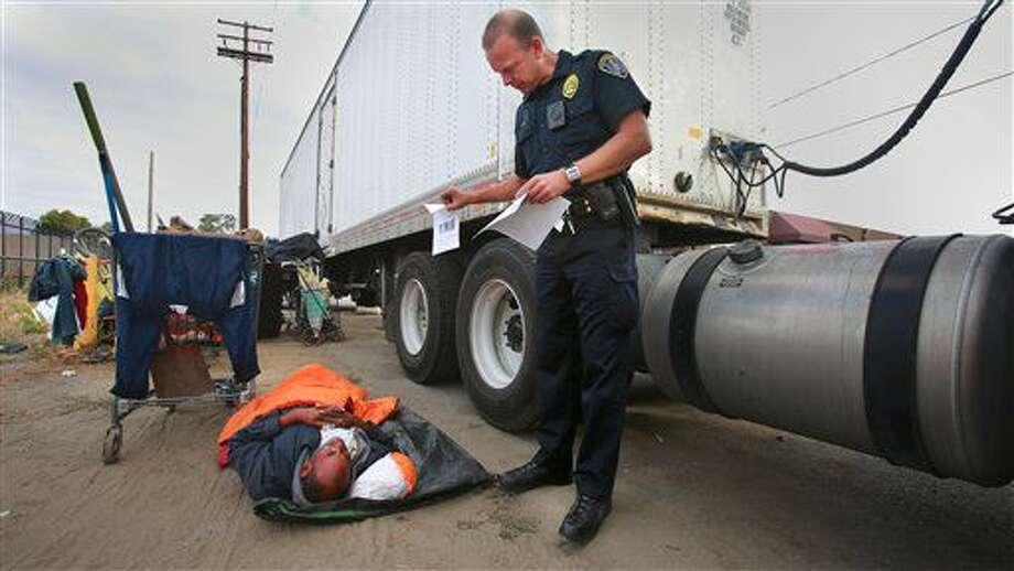 ARCHIVO - En esta imagen de archivo del 6 de julio de 2016, Ronald Mays, que se mueve para ver un folleto con imágenes de un sospechoso de ataques recientes contra personas sin hogar, mientras el agente Brian Lucchesi, del equipo de contacto con los indigentes en la policía de San Diego, visita varias zonas tras una serie de ataques en la región. (Peggy Peattie/U-T San Diego via AP, Archivo) Photo: Peggy Peattie