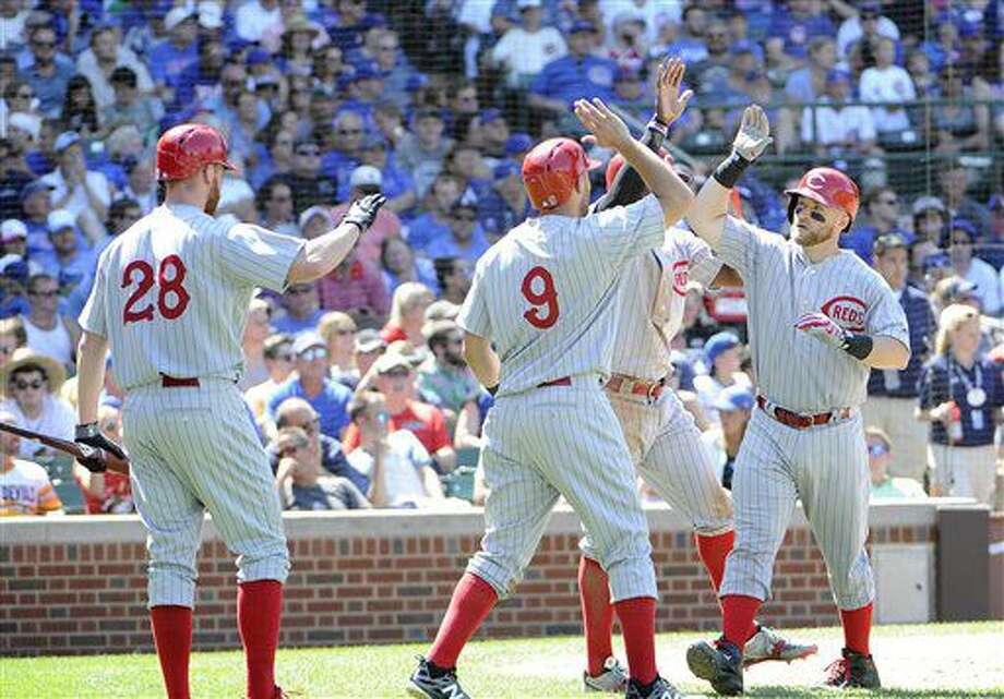 El jugador de los Rojos, Tucker Barnhart, derecha, es felicitado por compañeros tras batear un jonrón de tres carreras contra los Cachorros de Chicago el miércoles, 6 de julio de 2016, en Chicago. (AP Photo/David Banks) Photo: David Banks