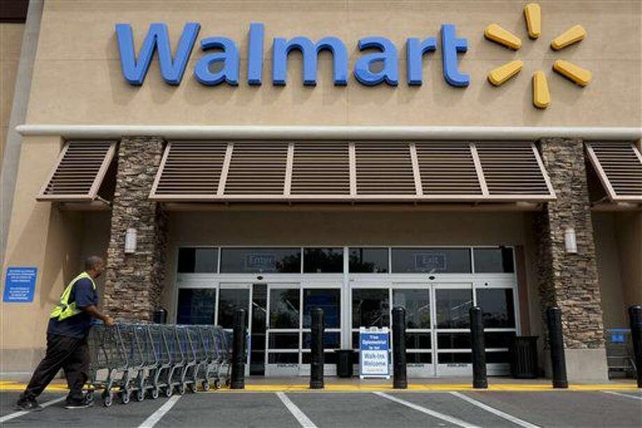 Esta foto tomada el 9 de mayo del 2013 muestra a un trabajador empujando carritos de compra enfrente de una tienda Wal-Mart en La Habra, California. Wal-Mart ahora permitirá que la gente pague con celulares en sus 4.600 tiendas en todo el país. Con Walmart Pay, el cajero escanea un código QR en la pantalla del celular para completar el pago. Esto es parte de la estrategia general de Wal-Mart para facilitar y agilizar las compras. (Foto AP /Jae C. Hong, Archivo) Photo: Jae C. Hong