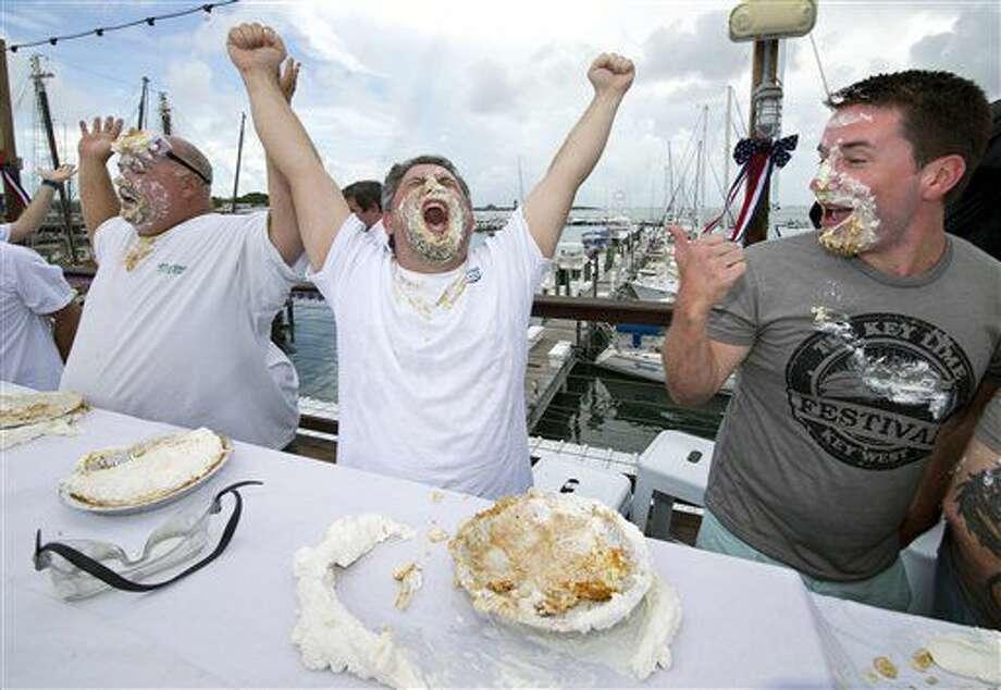En esta fotografía proporcionada por la Florida Keys News Bureau, Elliot Zeller, al centro, eleva sus manos para indicar que es el primer concursante en comerse todo un pie de lima durante el Concurso Mile High de Comedores de Pie de Lima de los Cayos, el lunes 4 de julio de 2016, en Key West, Florida. A la izquierda está Steve Carr, ganador del concurso en 2015 y segundo lugar este año. Zeller se comió un pie de de 22 centímetros (9 pulgadas) sin usar las manos en 62,62 segundos. Este evento anual se ha convertido en la respuesta de esta ciudad subtropical al concurso de comedores de hot dogs en la ciudad de Nueva York por el 4 de julio. (AP Foto/Florida Keys News Bureau, Rob O'Neal) Photo: Rob O'Neal