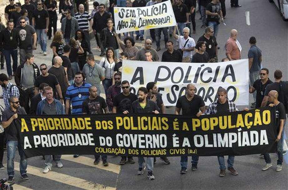 """Agentes policiales de Río de Janeiro demandan mejores condiciones de trabajo en una movilización que tuvo lugar el 27 de junio del 2016. El cartel de adelante dice """"La prioridad de la policía es la población, la prioridad del gobierno es la olimpiada"""". Los policías se quejan de que el gobierno está haciendo a un lado muchas necesidades del pueblo para costear los Juegos Olímpicos de Río. (AP Photo/Silvia Izquierdo) Photo: Silvia Izquierdo"""