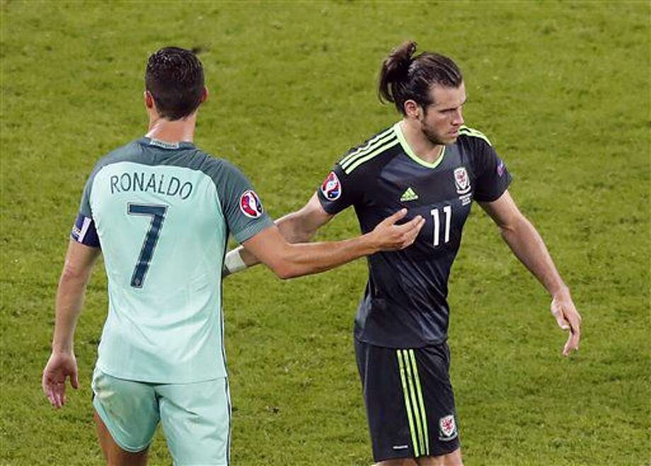 Portugal's Cristiano Ronaldo, left, conforts Wales' Gareth Bale at the end of the Euro 2016 semifinal soccer match between Portugal and Wales, at the Grand Stade in Decines-Charpieu, near Lyon, France, Wednesday, July 6, 2016. Cristiano Ronaldo led Portugal into its second European Championship final, scoring with a header and setting up Nani's goal soon after in a 2-0 win over Wales on Wednesday. (AP Photo/Francois Mori) Photo: Francois Mori