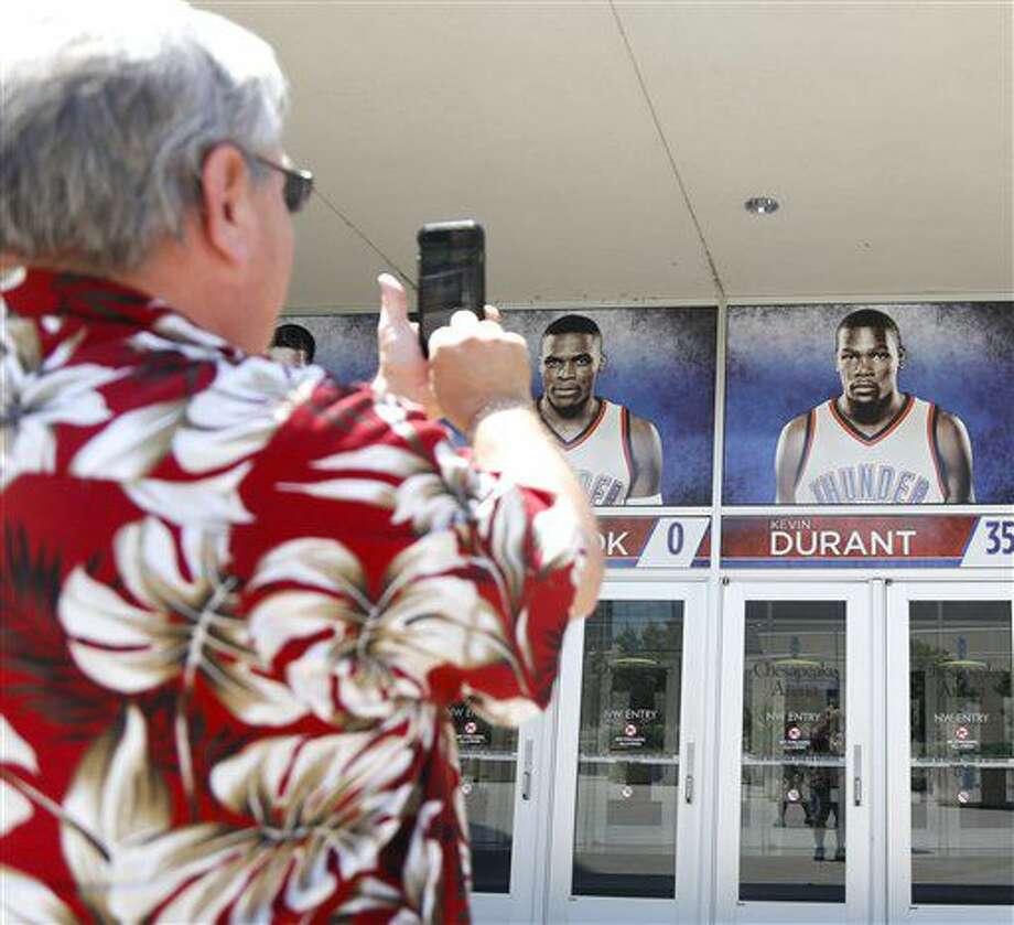 Una persona toma una fotografía del cartel de Kevin Durant, en una entrada de la Chesapeake Energy Arena en Oklahoma City, el lunes 4 de julio de 2016 (Kurt Steiss/The Oklahoman via AP) Photo: Kurt Steiss