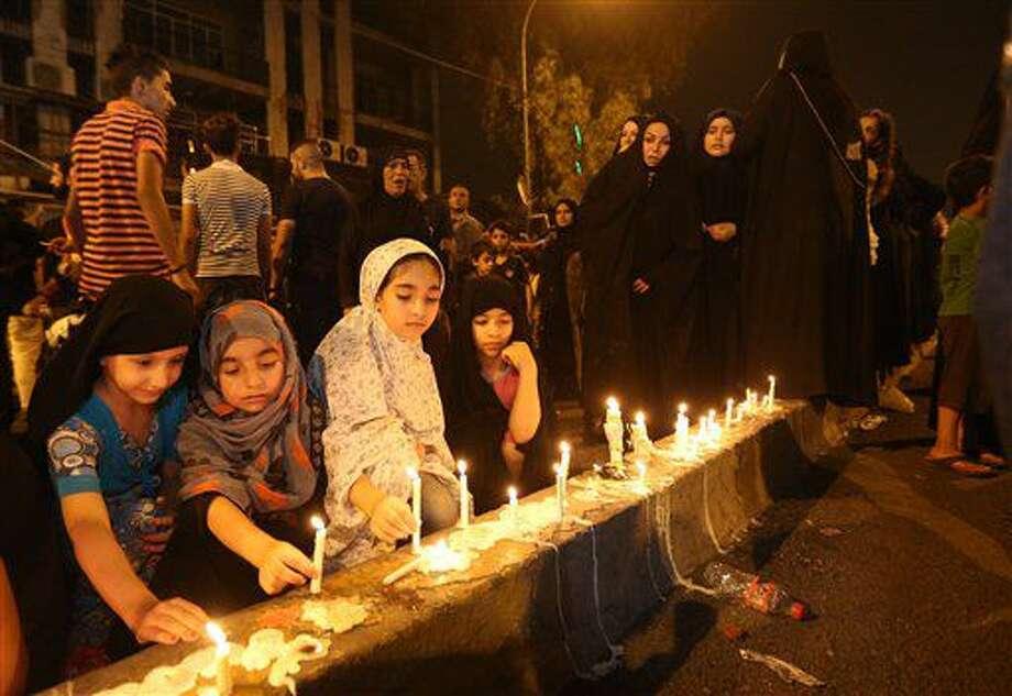 Varias personas encienden velas en el lugar de un atentado masivo en Karada, un concurrido distrito comercial donde muchas de las víctimas realizaban compras para el feriado del Eid al-Fitr, en el centro de Bagdad, Irak, el 4 de julio de 2016. (AP Foto/Hadi Mizban) Photo: Hadi Mizban