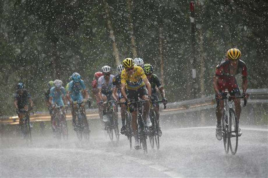 Australia's Richie Porte, right, breaks away from the group with Britain's Chris Froome, wearing the overall leader's yellow jersey, as they climb towards Andorra Arcalis in pouring rain and hail during the ninth stage of the Tour de France cycling race over 184.5 kilometers (114.3 miles) with start in Vielha Val d'Aran, Spain, and finish in Andorra Arcalis, Andorra, Sunday, July 10, 2016. (AP Photo/Christophe Ena) Photo: Christophe Ena