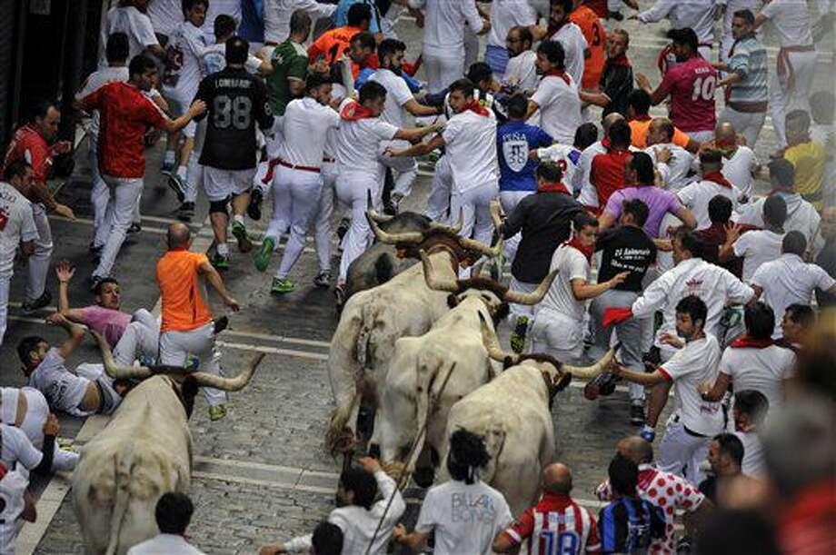Corredores junto a un toro bravo y varios cabestros de la ganadería José Escolar Gil en la calle Estafeta, durante el tercer encierro de las fiestas de San Fermín en Pamplona, en el norte de España, el sábado 9 de julio de 2016. (AP Foto/Alvaro Barrientos) Photo: Alvaro Barrientos