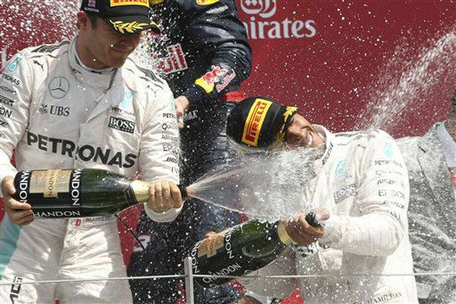 Mercedes driver Lewis Hamilton of Britain, winner, right, sprays champagne flanked by his teammate Nico Rosberg of Germany, sec on place, during the British Formula One Grand Prix at the Silverstone racetrack, Silverstone, England, Sunday, July 10, 2016. (AP Photo/Luca Bruno) Photo: Luca Bruno