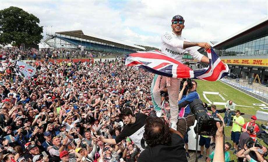 El piloto británico Lewis Hamilton, de la escudería Mercedes, festeja tras ganar el Gran Premio de Gran Bretaña de la Fórmula Uno en el circuito de Silverstone, Inglaterra, el domingo 10 de julio de 2016. (David Davies/PA via AP) Photo: David Davies