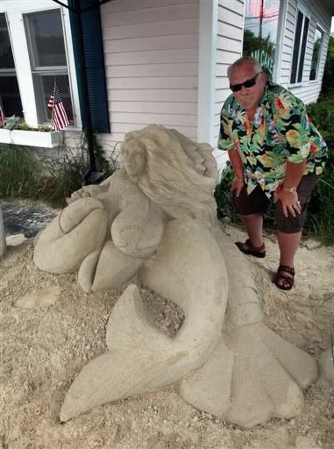 Salty's restaurant owner Raymond Roy poses for a photo in front of the restaurant with the mermaid sand sculpture in West Yarmouth, Mass. The mermaid sculpted from sand and placed outside the popular Cape Cod restaurant is raising eyebrows and triggering complaints.  Photo: Steve Haines | Cape Cod Times Via AP
