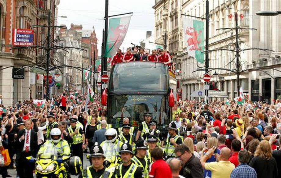 Wales soccer players ride atop an open top bus, with front left to right, Ashley Williams, Gareth Bale, manager Chris Coleman, acknowledge the crowd of fans during their homecoming in Cardiff City centre, Wales, Friday July 8, 2016. Wales return home to a hero's welcome after unexpectedly reaching the semi-finals of the Euro 2016 soccer championships knocked out by Portugal. (Paul Harding / PA via AP) Photo: Paul Harding