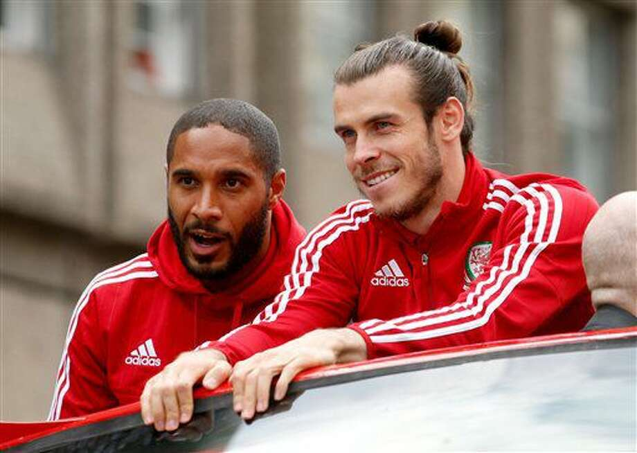 Wales soccer players ride an open top bus, with front left to right, Ashley Williams, Gareth Bale, as they acknowledge the crowd of fans during their homecoming in Cardiff City centre, Wales, Friday July 8, 2016. Wales return home to a hero's welcome after unexpectedly reaching the semi-finals of the Euro 2016 soccer championships knocked out by Portugal but refreshing Welsh pride. (Paul Harding / PA via AP) Photo: Paul Harding
