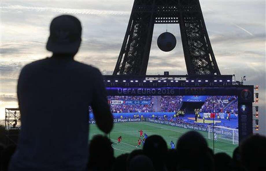 Hinchas miran la final de la Eurocopa entre Francia y Portugal en una pantalla gigante cerca de la Torre Eiffel el domingo, 10 de julio de 2016, en París. (AP Photo/Laurent Cipriani) Photo: Laurent Cipriani