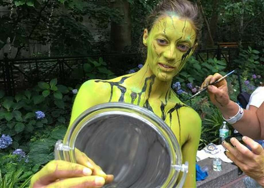 Megan Slawkawski looks at her reflection as bodypainter artist Uta Brauser applies paint at the third annual NYC Bodypainting Day on Saturday. Dozens of artists used the naked bodies as canvases for the event, which celebrates freedom of artistic expression and body acceptance. Photo: Dino Hazell | AP: Photo