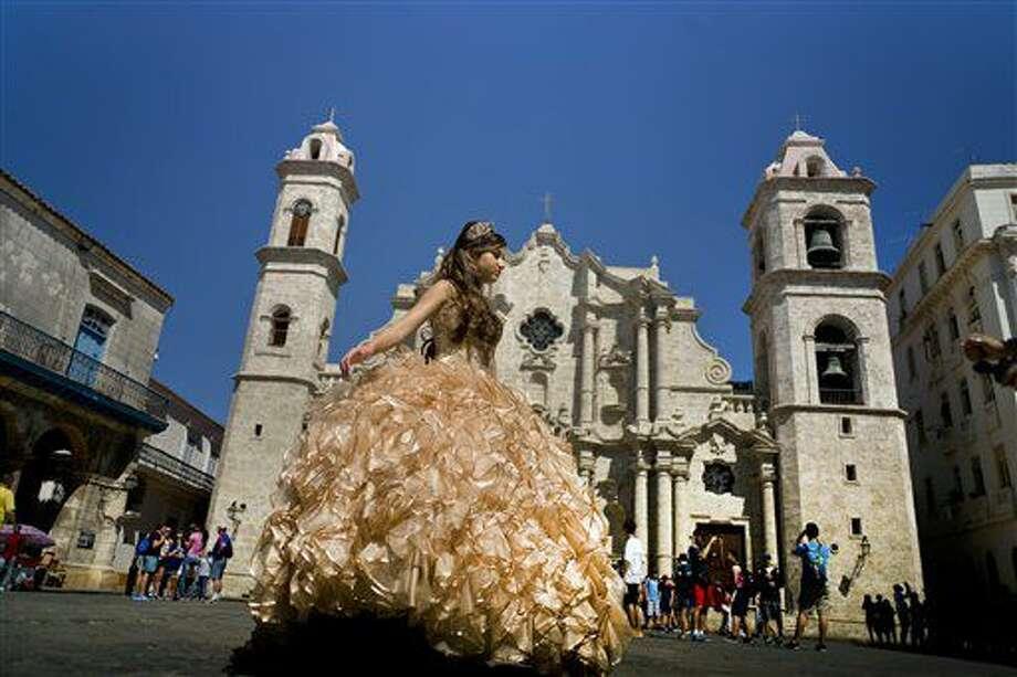 Foto tomada el 14 de marzo del 2016 de una quinceañera posando para el fotógrafo frente a una catedral donde turistas hacen fila para entrar, en La Habana. (AP Foto/Ramon Espinosa, File) Photo: Ramon Espinosa