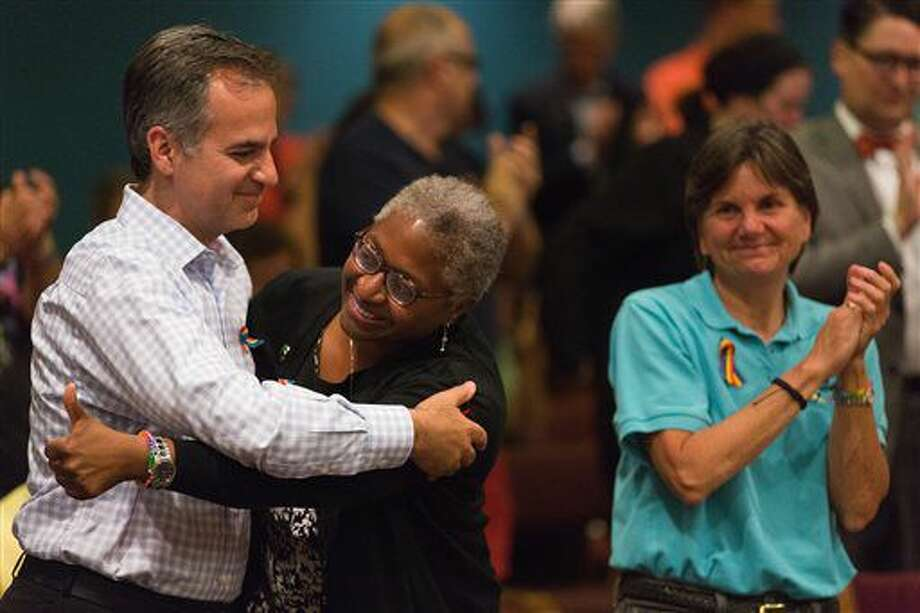 Gary Pilnick, vice chairmen of Kellogg Company, left, hugs Cheryl Gilliam, vice president of Kalamazoo Gay Lesbian Resource Center, as Kathy Greaves, right, watches after Portage City Council voted 6-1 to pass a new ordinance that protects the LGBTQ community from being discriminated against at Portage City Hall in Portage, Mich., Tuesday, June 28, 2016. (Bryan Bennett/Kalamazoo Gazette-MLive Media Group via AP) MANDATORY CREDIT Photo: Bryan Bennett