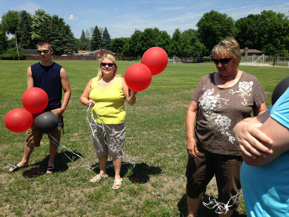 From left, Justin Monville, Anne Hinson and Julie Gamm take part in the remembrance of Parkdale Elementary School and Seth Enszer, a classmate who died recently. Photo: Photo Courtesy Of Ali Geer