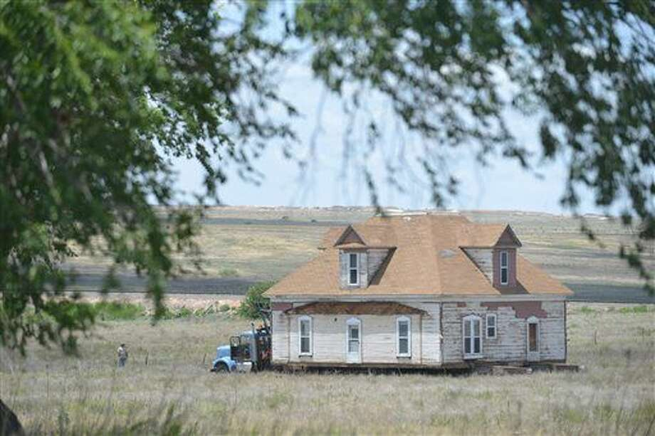 In a Monday, June 27, 2016 photo, house owner Paul Burks and crews with McDowell House and Structure Moving haul a historic 1900s home across an 80-acre pasture outside Canyon to its new location off Highway 60. The historic house was the home of W.F. Heller, a Civil War veteran and the first to farm in the area successfully in the late 1800s. (Michael Schumacher/Amarillo Globe-News via AP) Photo: Michael Schumacher
