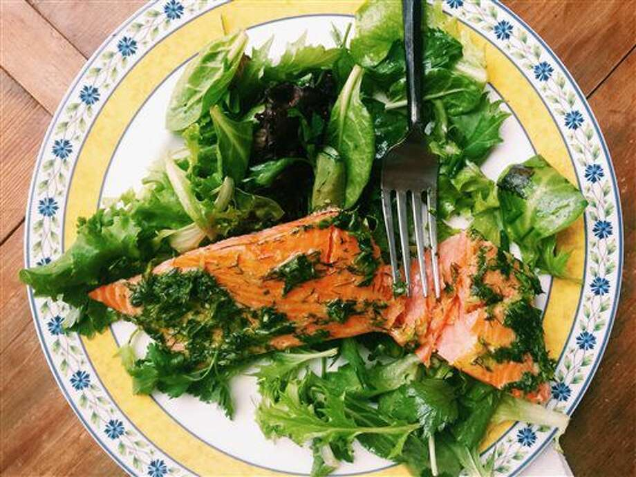 This May 13, 2016 photos a fillet of salmon smothered in an herb marinade served over a tender green salad, in New Milford, Conn. This warm-weather recipe combines salmon bathed in olive oil and herbs with spring-y greens and salad. It's the kind of lighter, brighter meal we tend to want during summer. (AP Photo/Katie Workman) Photo: Katie Workman