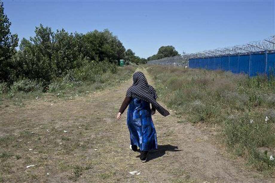 Una mujer camina junto a una valla fronteriza en un asentamiento improvisado para migrantes y refugiados situado a pocos metros de la frontera entre Serbia y Hungría, en Horgos, Serbia, el 4 de julio de 2016. (AP Foto/Marko Drobnjakovic) Photo: Marko Drobnjakovic