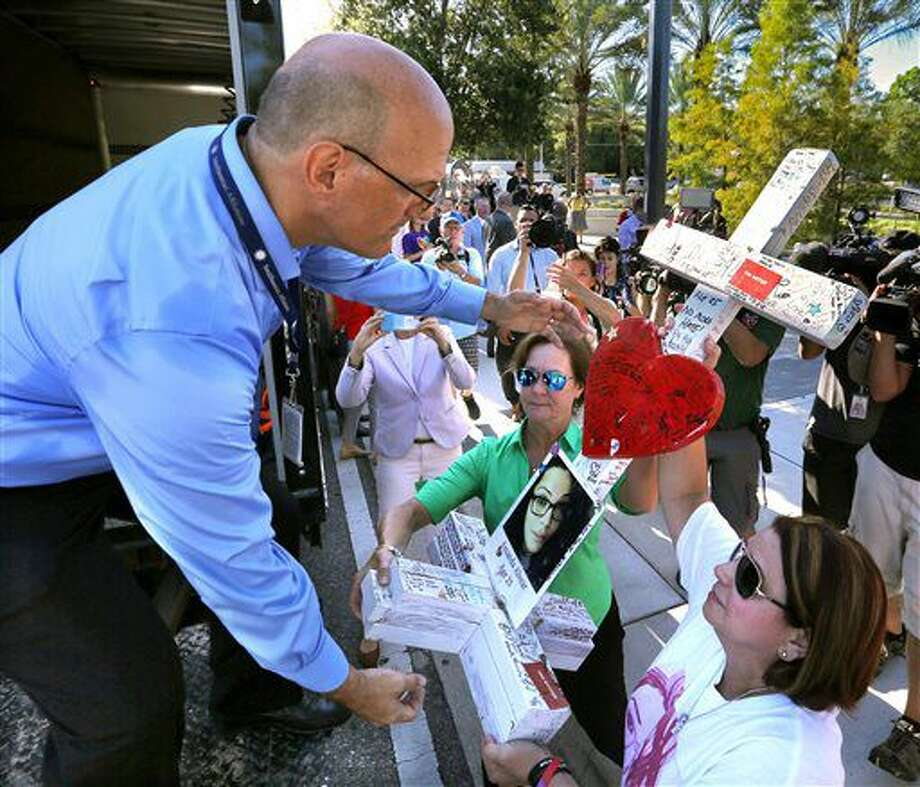 On the one-month anniversary of the Pulse nightclub massacre in Orlando, Fla., the mother of victim Amanda Alvear, Mayra Alvear, right, and Amanda's aunt, Robin Alvear, center, hand off the cross that was erected in Amanda's honor to Michael Perkins, left, of the Orange County Regional History Center, during a somber ceremony at Orlando Regional Medical Center, near the club, Tuesday, July 12, 2016. The 49 crosses were made by a Chicago carpenter to honor each of the victims killed at Pulse on June 12. The crosses will be on permanent display at the history center in downtown Orlando. (Joe Burbank/Orlando Sentinel via AP) Photo: Joe Burbank