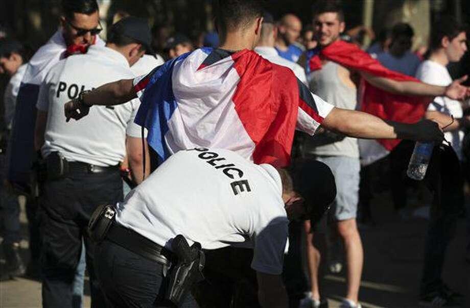 Policías revisan a aficionados franceses en la fan zone de París previo a la semifinal de la Eurocopa entre Alemania y Francia, el jueves 7 de julio de 2016. (AP Foto/Kamil Zihnioglu) Photo: Kamil Zihnioglu