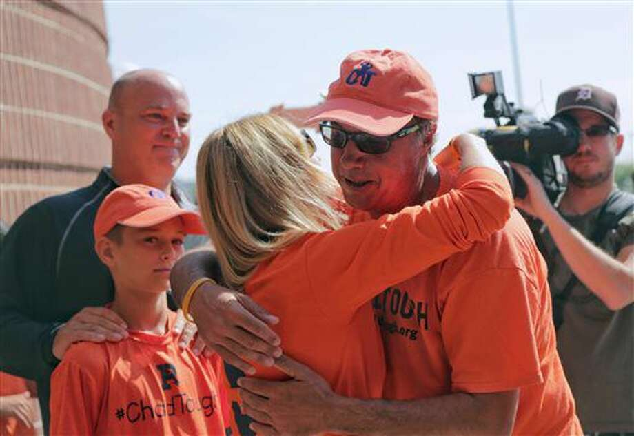 Jim Burns of Souderton, Pa., hugs Tammi Carr as her son CJ Carr and husband Jason Carr look on as Burns makes the end of his 600-mile walk from Philadelphia to Ann Arbor to raise awareness for ChadTough Foundation at Michigan Stadium in Ann Arbor, Mich., on Monday July 11, 2016. Chad Carr died aged five after a 15 month battle with Diffuse Intrinsic Pontine Glioma, a brain cancer. (Ryan Garza/Detroit Free Press via AP) Photo: Ryan Garza