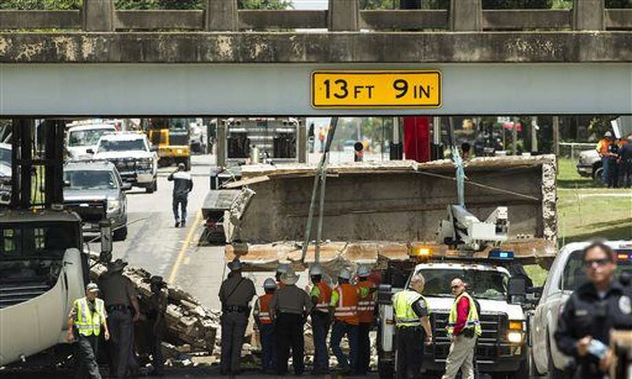 Police and Texas Department of Transporation officials investigate the scene of a bridge collapse on Thursday, July 7, 2016, in Sealy, Texas. Investigators say a child riding in the front seat of a car was killed when part of a Central Texas highway bridge collapsed after being hit by a truck. (Brett Coomer/Houston Chronicle via AP) Photo: Brett Coomer