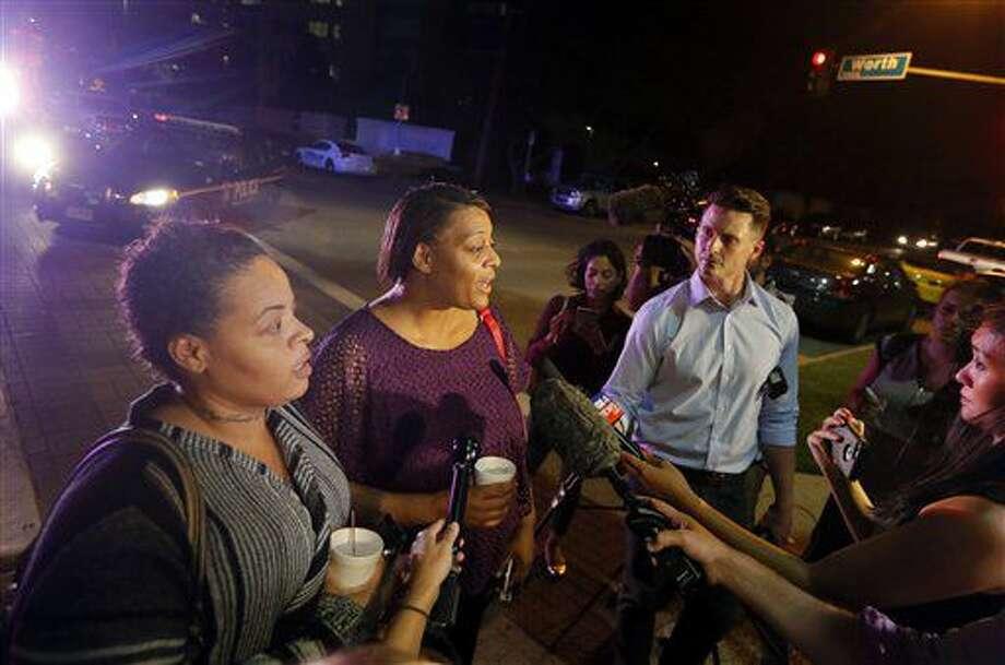 Sherie Williams, a la izquierda, y Theresa Williams, al centro, conversan con la prensa cuando se retiraban del Centro Médico de la Universidad Baylor en Dallas, el viernes 8 de julio de 2016. Theresa Williams dijo que su hermana Shetamia Taylor, que asistía a una movilización con sus cuatro hijos adolescentes en el centro de Dallas, fue herida de bala en una pierna. (AP Foto/Tony Gutiérrez) Photo: Tony Gutierrez