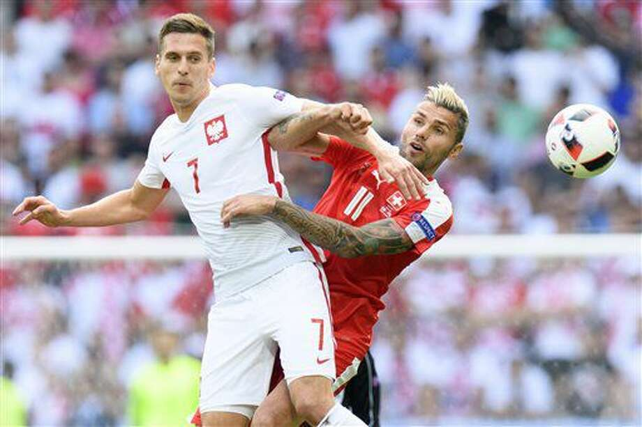 Switzerland's Valon Behrami, right, and Poland's Arkadiusz Milik challenge for the ball during the Euro 2016 round of 16 soccer match between Switzerland and Poland, at the Geoffroy Guichard stadium in Saint-Etienne, France, Saturday, June 25, 2016. (Jean-Christophe Bott/Keystone via AP) Photo: Michael Sohn