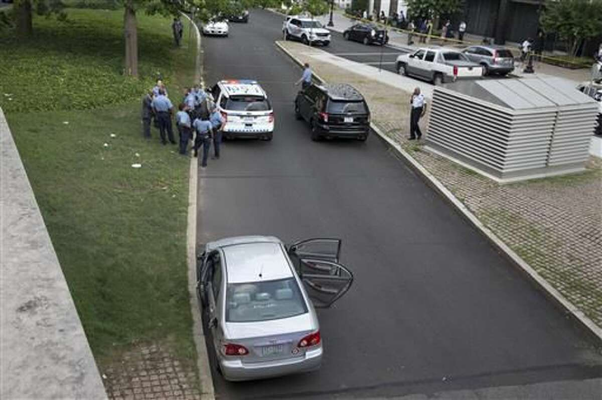 As police officers gather in the background, a car sits with its doors open near the U.S. Capitol in Washington, Tuesday, July 12, 2016. The U.S. Capitol and its office buildings were briefly locked down after District of Columbia police stopped the car about two blocks from the Capitol and took three people into custody, Police Chief Cathy Lanier told reporters at the scene. Lanier said one of the people inside the car fired at officers during the pursuit, and officers did not fire back. Lanier described the weapon as