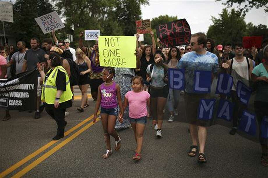 People march after some of them spoke in front of the St. Anthony Police Department in St. Anthony, Minn., Sunday, July 10, 2016. (Jeff Wheeler/Star Tribune via AP) Photo: Jeff Wheeler