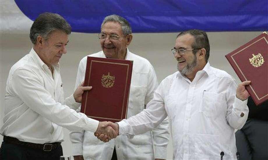 ARCHIVO - En esta foto de archivo del 23 de junio de 2016, el presidente colombiano Juan Manuel Santos, a la izquierda, y el comandante Timoleón Jiménez, de las Fuerzas Armadas Revolucionarias de Colombia, estrechan las manos durante la ceremonia de firma de un acuerdo para un alto el fuego y el desarme de la guerrilla, efectuada en La Habana, Cuba. Al centro, el presidente cubano Raúl Castro. El gobierno colombiano anunció que el ejército y la guerrilla escenificaron un enfrentamiento armado el viernes 8 de julio. La insurgencia afirma que sus efectivos aguardaban una comisión de Naciones Unidas cuando los atacó el ejército. (AP Foto/Ramón Espinosa, Archivo) Photo: Ramon Espinosa