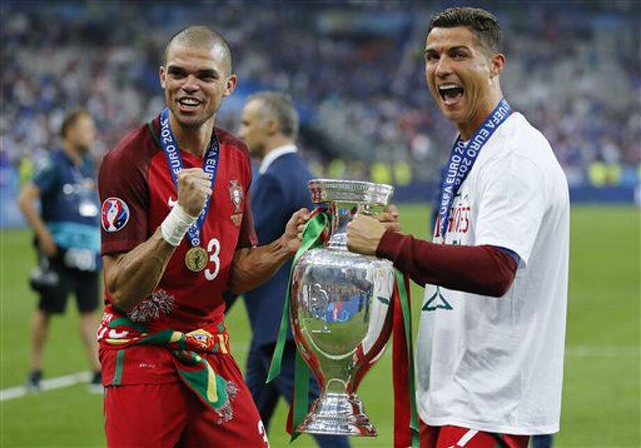 Portugal's Cristiano Ronaldo, right, and Pepe celebrate with the trophy at the end of the Euro 2016 final soccer match between Portugal and France at the Stade de France in Saint-Denis, north of Paris, Sunday, July 10, 2016. Portugal won 1-0. (AP Photo/Frank Augstein) Photo: Frank Augstein