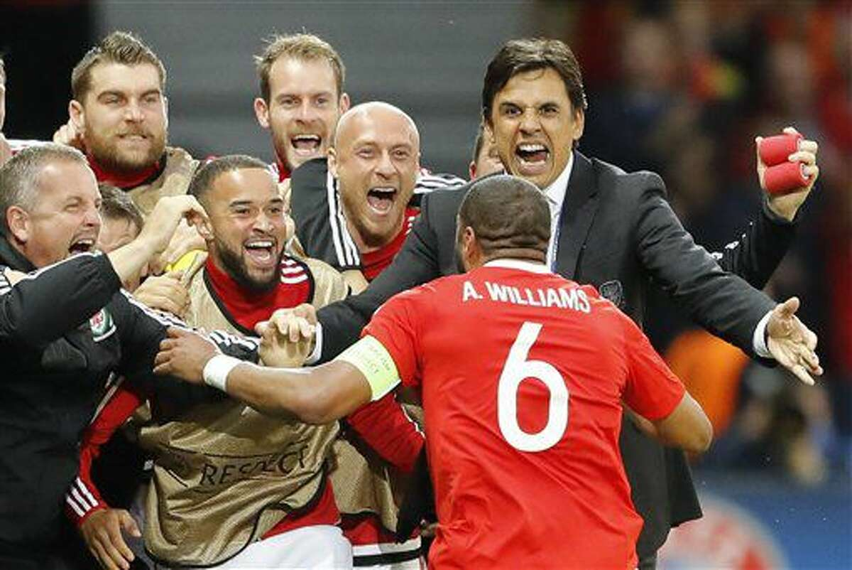 Wales coach Chris Coleman, right, congratulates Wales' Ashley Williams after scoring their first goal during the Euro 2016 quarterfinal soccer match between Wales and Belgium, at the Pierre Mauroy stadium in Villeneuve d'Ascq, near Lille, France, Friday, July 1, 2016. (AP Photo/Frank Augstein)