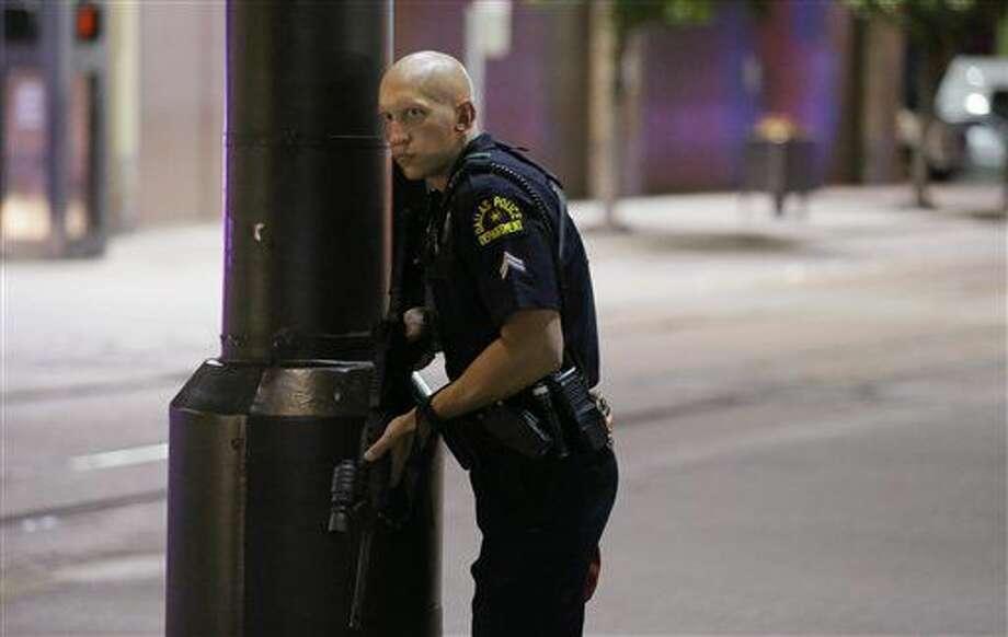 Un policía de Dallas monta guardia en una calle en el centro de Dallas, el jueves 7 de julio de 2016, tras noticias sobre disparos durante una protesta por la muerte de dos hombres negros por disparos de la policía en Louisiana y Minnesota. (AP Foto/LM Otero) Photo: LM Otero