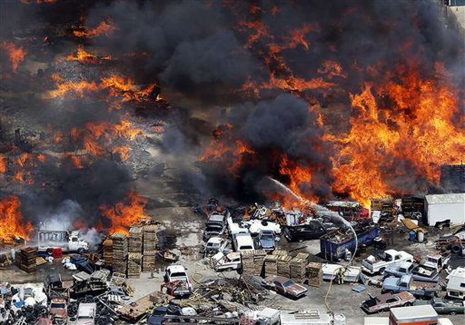 Firefighters battle a large fire at a commercial storage yard in Salt Lake City. Friday, July 8, 2016. The storage blaze led to a grass fire on fields around Interstate-80. (Ravell Call,/The Deseret News via AP) Photo: Ravell Call