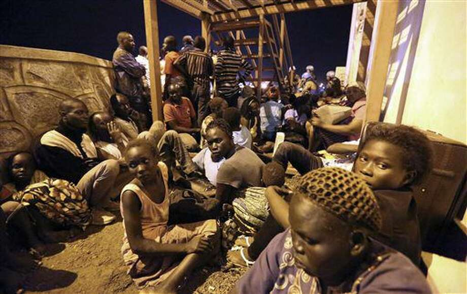 In this photo taken late Friday, July 8, 2016 and released by the United Nations Mission in South Sudan (UNMISS), villagers huddle for safety from the fighting between buildings near the UN base and compound in the capital Juba, South Sudan. The president of South Sudan and his opposition rival both called Monday for a cease-fire in a conflict that has seen fierce clashes between their forces spread from the capital to a southeastern town. (Eric Kanalstein/UNMISS via AP) Photo: Eric Kanalstein