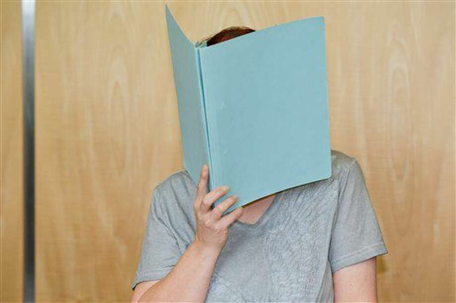 Defendant Andrea G. , who is accused of murder, covering her face with a folder, in the court room of the regional court in Coburg, Germany, Tuesday July 12, 2016. A couple have gone on trial in Germany after the remains of eight babies were found at their apartment in Bavaria last year. The 45-year-old mother, identified only as Andrea G., is charged with four counts of murder in the trial at the Coburg state court and her 55-year-old husband, Johann G., with being an accessory to murder. (Daniel Karmann/dpa via AP) Photo: Daniel Karmann