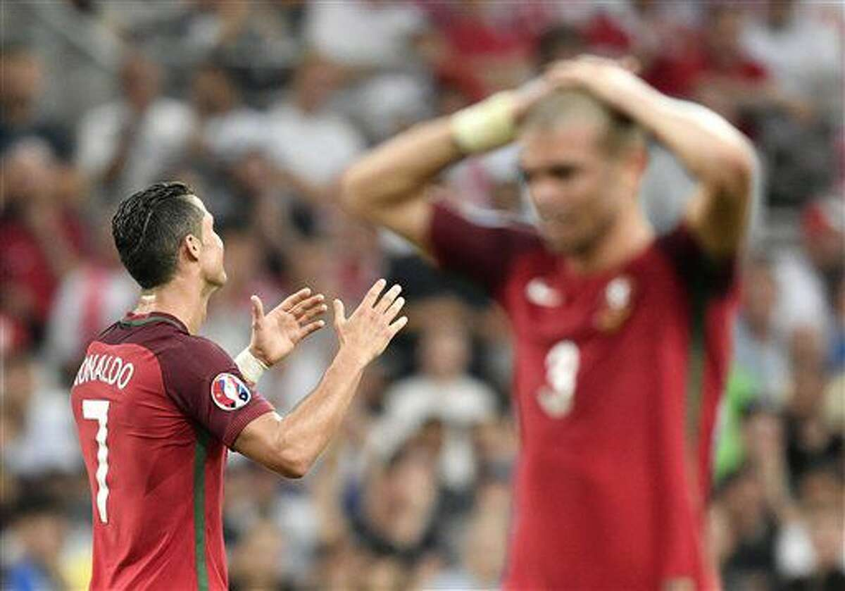 Portugal's Cristiano Ronaldo, left, and Pepe raise their arms during the Euro 2016 quarterfinal soccer match between Poland and Portugal, at the Velodrome stadium in Marseille, France, Thursday, June 30, 2016. (AP Photo/Martin Meissner)