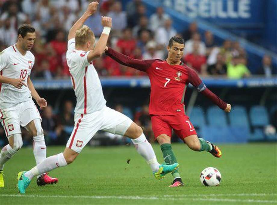 Portugal's Cristiano Ronaldo, right, takes a shot next to Poland's Kamil Glik, center, during the Euro 2016 quarterfinal soccer match between Poland and Portugal, at the Velodrome stadium in Marseille, France, Thursday, June 30, 2016. (AP Photo/Petr David Josek) Photo: STF