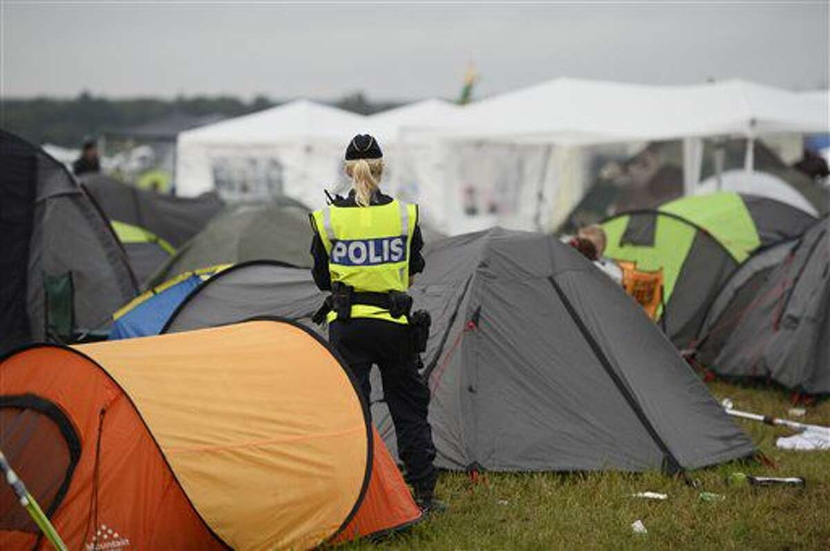 In this photo dated Saturday July 2, 2016, a police officer helps with security in the campsite at Bravalla Festival in Norrkoping, Sweden, on Saturday July 2, 2016. Swedish police told the media that they are investigating five cases of alleged rape and more than a dozen suspected sexual assaults committed at the Bravalla Festival over last weekend. (Izabelle Nordfjell / TT via AP)