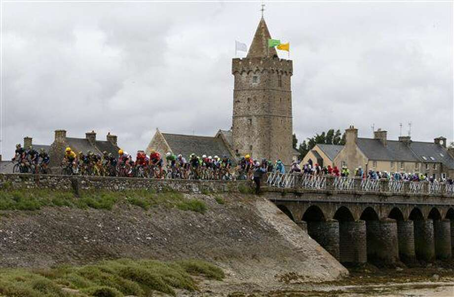 The pack rides on a bridge during the second stage of the Tour de France cycling race over 183 kilometers (113.7 miles) with start in Saint-Lo and finish in Cherbourg-en-Cotentin, France, Sunday, July 3, 2016. (AP Photo/Peter Dejong) Photo: Peter Dejong