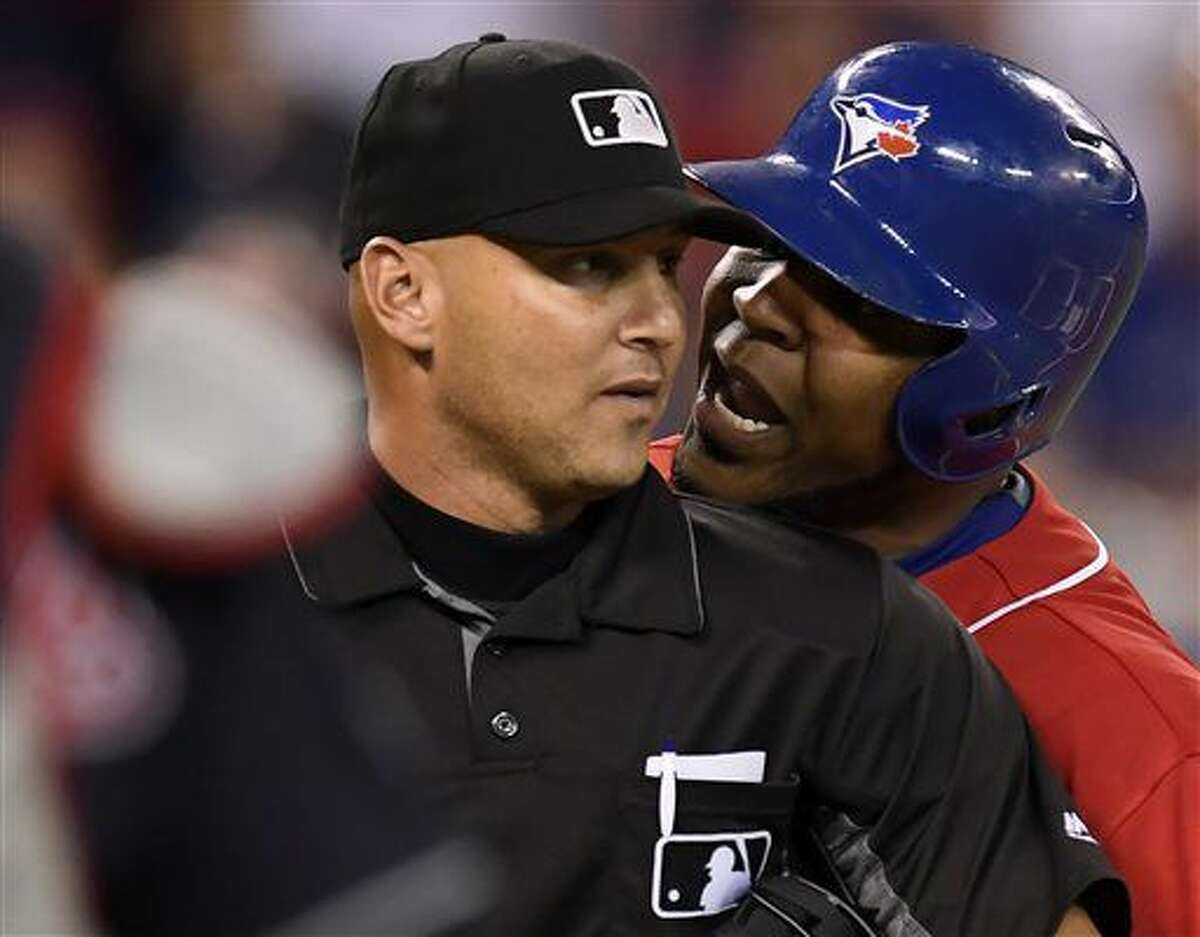 Toronto Blue Jays designated hitter Edwin Encarnacion exchanges words with umpire Vic Carapazza, left, before Encarnacion was ejected from the game over a call-out dispute on strikes during the first inning of a baseball against the Cleveland Indians in Toronto., Friday, July 1, 2016. (Frank Gunn/The Canadian Press via AP)