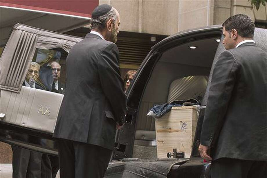 """Cantor Joseph Malovany pray in front of Elie Wiesel's coffin during a private service for the Nobel laureate and Holocaust survivor at the Fifth Avenue Synagogue in New York, Sunday, July 3, 2016. Wiesel shared the harrowing story of his internment at Auschwitz as a teenager through his classic memoir """"Night,"""" one of the most widely read and discussed books of the 20th century. (AP Photo/Andres Kudacki) Photo: Andres Kudacki"""