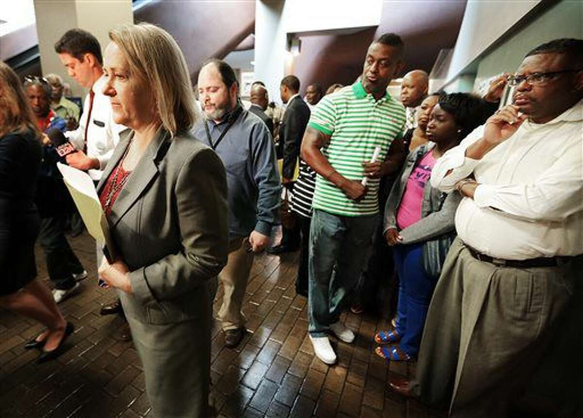 Assistant District Attorney Jennifer Nichols, left, leads reporters away for a short press conference as family members of Shanynthia Gardner wait for the defense attorney after her video hearing in Judge Loyce Lambert Ryan's court Tuesday, July 5, 2016, in Memphis. The 29-year-old is charged in the fatal stabbings of her four children. (Jim Weber/The Commercial Appeal via AP)