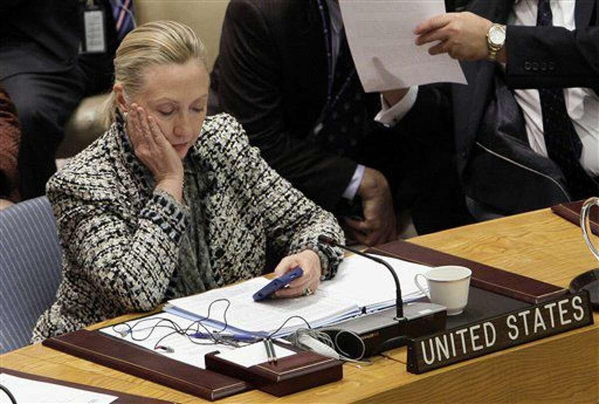 En esta imagen de archivo, tomada el 12 de marzo de 2012, la entonces secretaria de Estado de Estados Unidos, Hillary Clinton, consulta su celular durante una reunión del Consejo de Seguridad de Naciones Unidas en la sede del ente. La entrevista de Hillary Clinton con el FBI el 2 de julio de 2016 podría indicar que el Departamento de Justicia de Estados Unidos estaría cerca de concluir su investigación de un año de duración sobre el uso de un servidor privado para enviar correos electrónicos durante su etapa como secretaria de Estado. (AP Foto/Richard Drew, archivo)