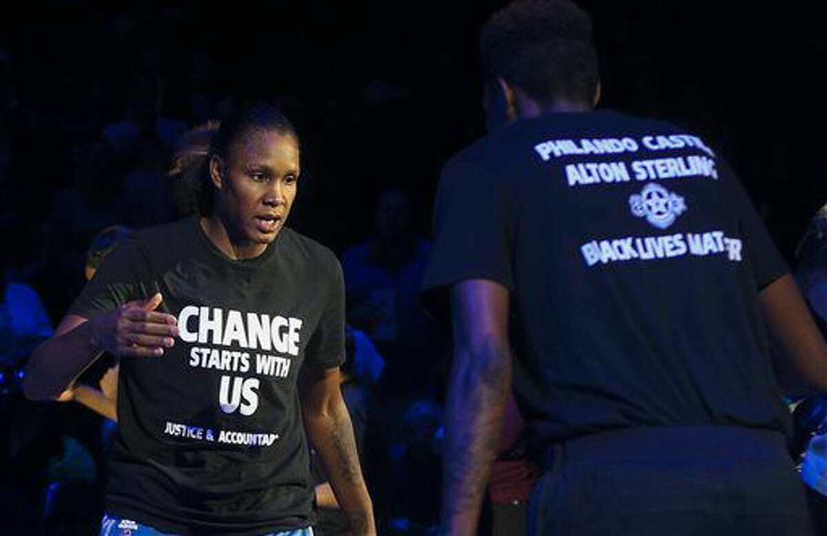 Minnesota Lynx forward Rebekkah Brunson (32) is greeted by Minnesota Lynx forward Natasha Howard (3) while starting lineups are announced at the Target Center on Saturday, July 9, 2016. Lynx players did not wear T-shirts supporting the Black Lives Matter movement ahead of Tuesday's game in San Antonio after four off-duty police officers walked away from security jobs at a Lynx game over the weekend because of the T-shirts. (Timothy Nwachukwu/Star Tribune via AP)
