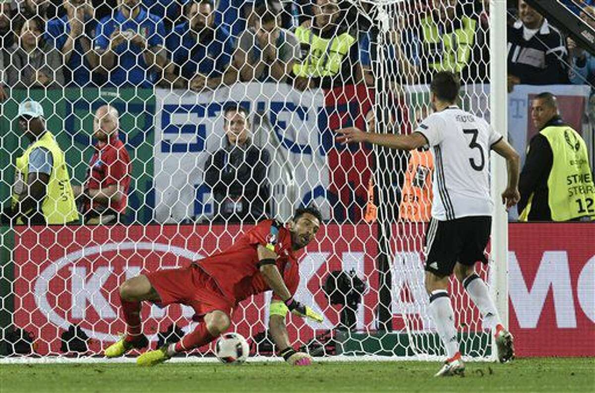 Germany's Jonas Hector scores the winning penalty past Italy goalkeeper Gianluigi Buffon during the Euro 2016 quarterfinal soccer match between Germany and Italy, at the Nouveau Stade in Bordeaux, France, Saturday, July 2, 2016. Germany defeated Italy 6-5 in a penalty shootout after the game ended tied 1-1. (AP Photo/Martin Meissner)